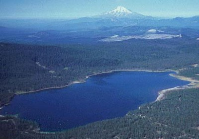 Fig 3. Medicine Lake, the collapse caldera structure at the summit of Medicine Lake Volcano with Mount Shasta 50 km away in the background. (kitezombies.com)
