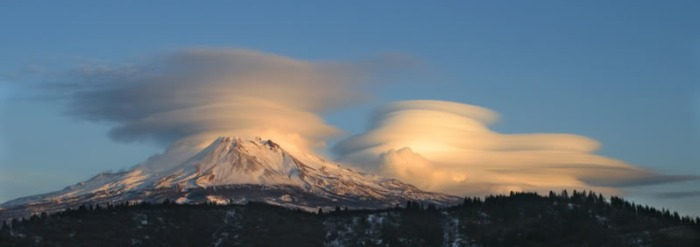 Fig 3. Mount Shasta often experiences strange weather phenomena. Here, Shasta is hidden by clouds whereas the cone of Shastina is clearly visible. Visible also in the foreground is the remains of the absolutely massive debris avalanche dated to between 300 and 380 kA that resulted from the collapse and total destruction of the ancestral cone. (summitpost.org)