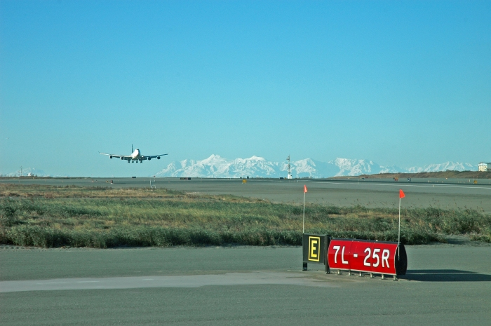 FedEx Jumbo jet landing at Ted Stevens International Airport.  Mount Spurr in the distance. Photographer Game McGimsey, the Alaska Volcano Observatory/US Geological Survey