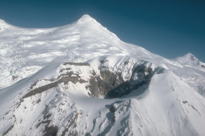 Crater Peak, a satellite vent of Mount Spurr volcano, and the snow- and ice-covered summit lava dome complex of Mount Spurr beyond. View is to the north. Photograph by R. McGimsey (U.S. Geological Survey)