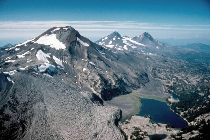 Fig 1. The Three Sisters volcanoes in Oregon from left to right they are Charity (South Sister), Hope (Middle Sister) and Faith (North Sister). Below South Sister is scenic Green Lake and on her flank the massive Newberry lava flow. (CVO)