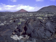 Lava field on El Hierro with a couple of volcanic cones in the background.