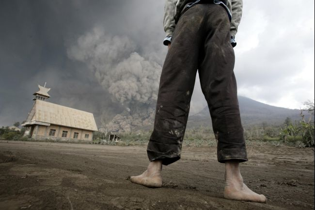Farmer with the deadly pyroclastic flow in the background.