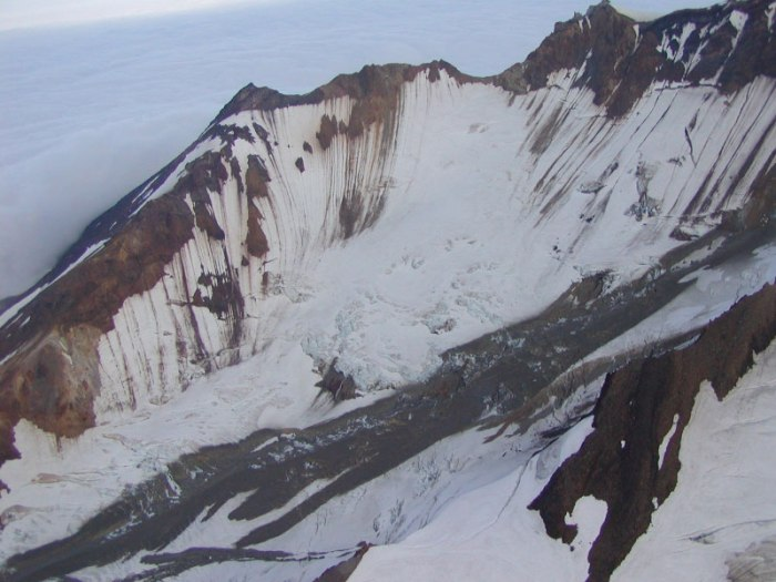 Flow lobes of a dark gray, clay-rich lahar can be seen down the length of the south glacier at Chiginagak Volcano.  The lahar deposits resulted from the draining of the summit caldera lake sometime in early summer 2005. Image courtesy Janet Schaefer, AVO / USGS, August 20, 2005  http://www.avo.alaska.edu/images/image.php?id=3329