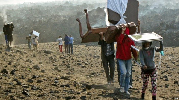Residents from the villages down in the caldera carry their important belongings uphill to save them from being burnt by the fast advancing lava. Photo: BBC
